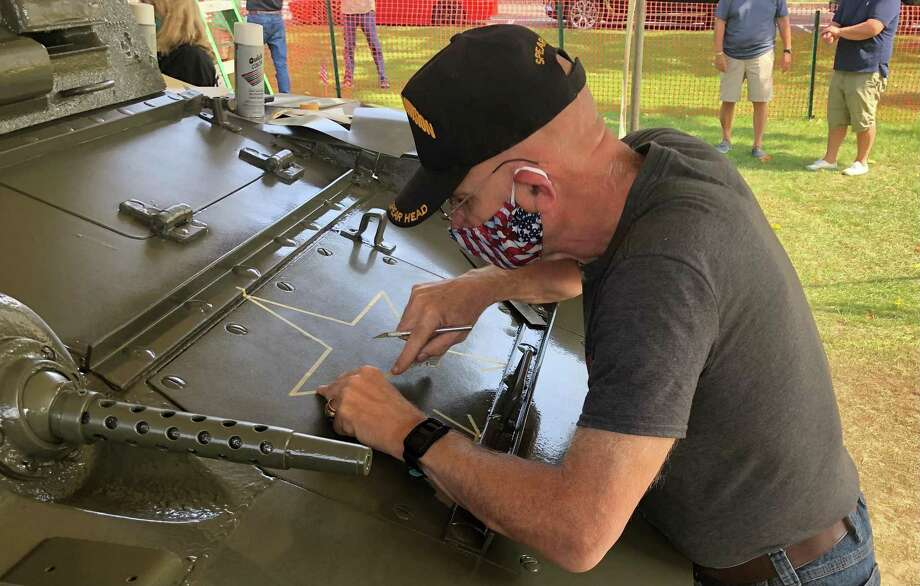 Bob Thomas of the United States Army Brotherhood of Tankers, which preserves and publicizes the history of the United States Army Armored Forces and other related services, stencils the outlines of stars and numbers that were painted on the tank. Photo: Deborah Rose /Hearst Connecticut Media / Danbury News Times