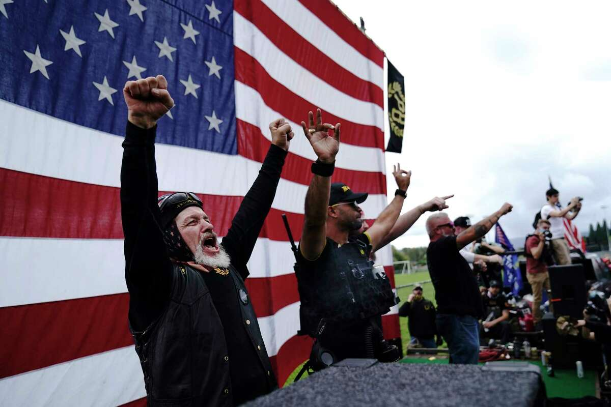 """FILE - Members of the Proud Boys cheer on stage as they and other right-wing demonstrators rally, Saturday, Sept. 26, 2020, in Portland, Ore. President Donald Trump didn't condemn white supremacist groups and their role in violence in some American cities this summer. Instead, he said the violence is a """"left-wing"""" problem and he told one far-right extremist group to """"stand back and stand by."""" His comments Tuesday night were in response to debate moderator Chris Wallace asking if he would condemn white supremacists and militia groups. Trump's exchange with Democrat Joe Biden left the extremist group Proud Boys celebrating what some of its members saw as tacit approval."""