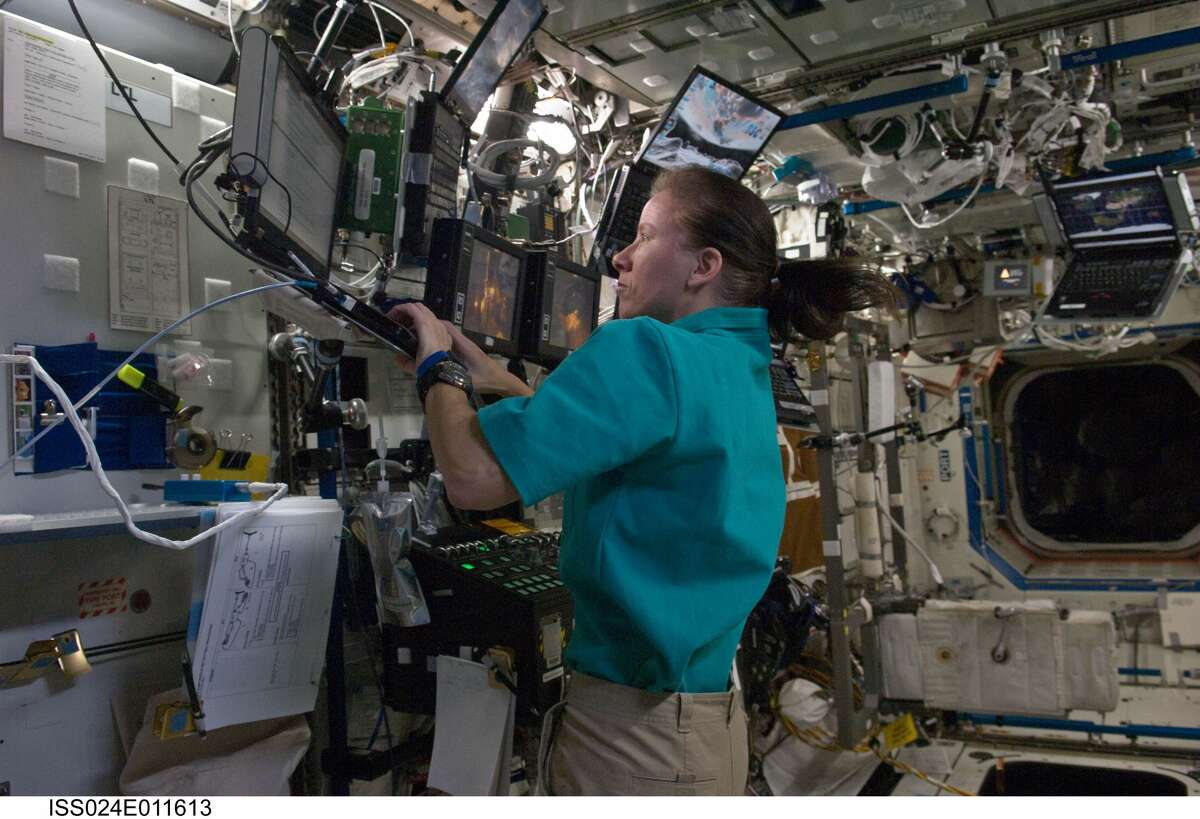 NASA astronaut Shannon Walker uses a computer near a robotic workstation in the Destiny laboratory of the International Space Station on Aug. 7, 2010. While not voting in this picture, Walker will use email to cast her ballot from space on Nov. 3, 2020.