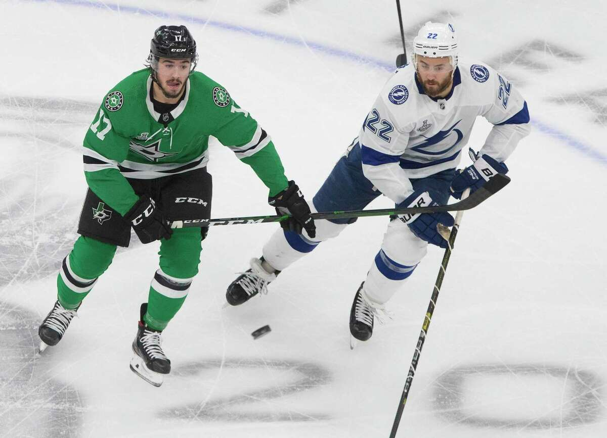 Tampa Bay Lightning's Kevin Shattenkirk (22) and Dallas Stars' Nick Caamano (17) battle for the puck during first-period NHL Stanley Cup finals hockey game action in Edmonton, Alberta, Monday, Sept. 28, 2020.