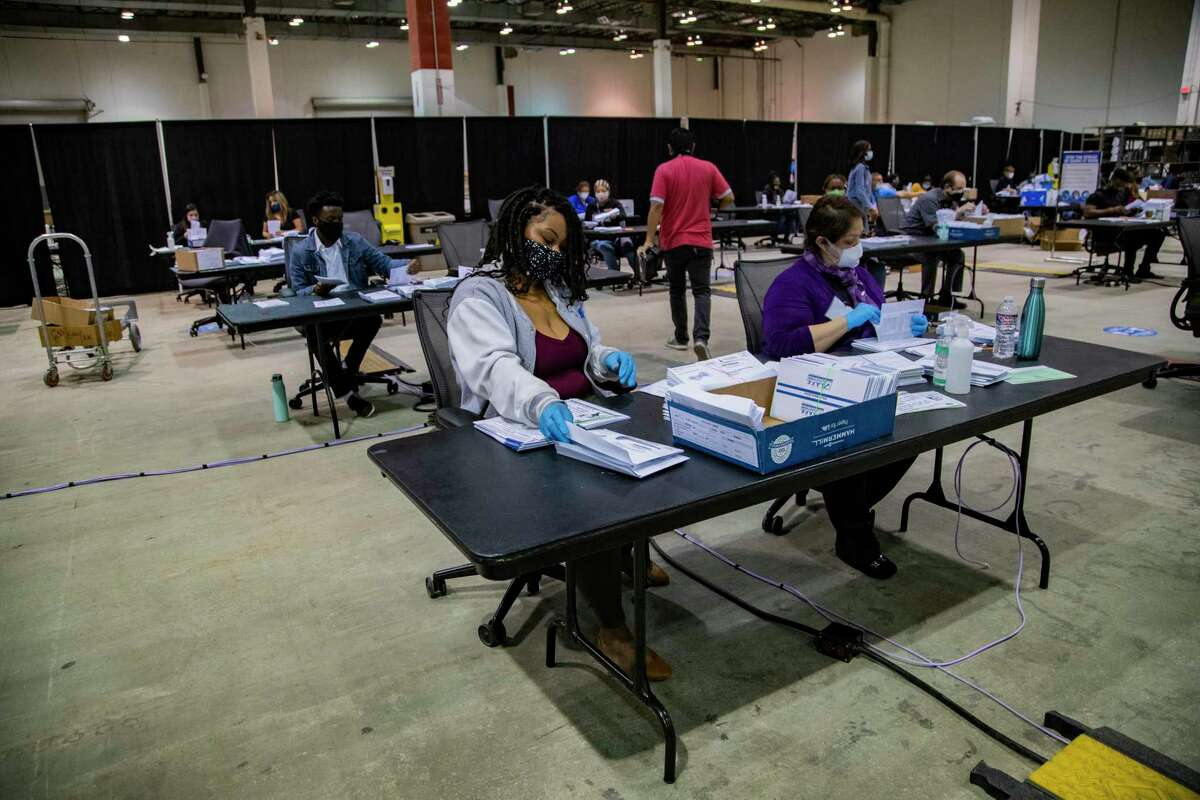 Harris County voting clerk Crystal Lillie, 35, combines the different paperwork that goes inside a ballot envelope in preparation for early voting, Friday, Sept. 25, 2020, in Houston.