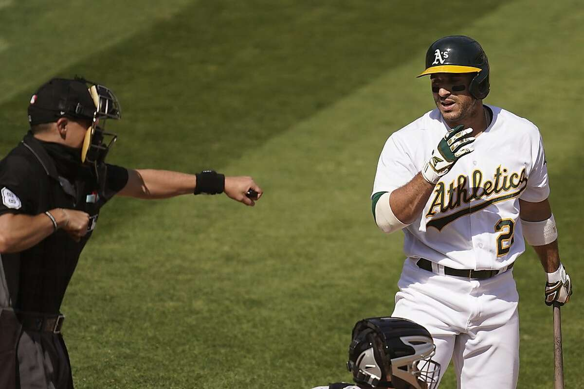 Home plate umpire Adam Hamari, left, gestures after Oakland Athletics' Ramon Laureano, right, struck out against Chicago White Sox pitcher Lucas Giolito during the sixth inning of Game 1 of an American League wild-card baseball series Tuesday, Sept. 29, 2020, in Oakland, Calif. (AP Photo/Eric Risberg)