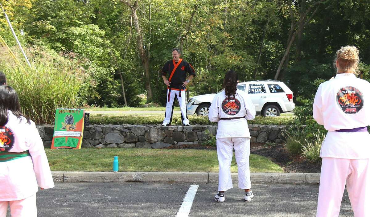 Mike Meyer, president of SDSS Martial Arts, works with students at the outdoor space the business now has available in the Wilton River Park Shopping Center.