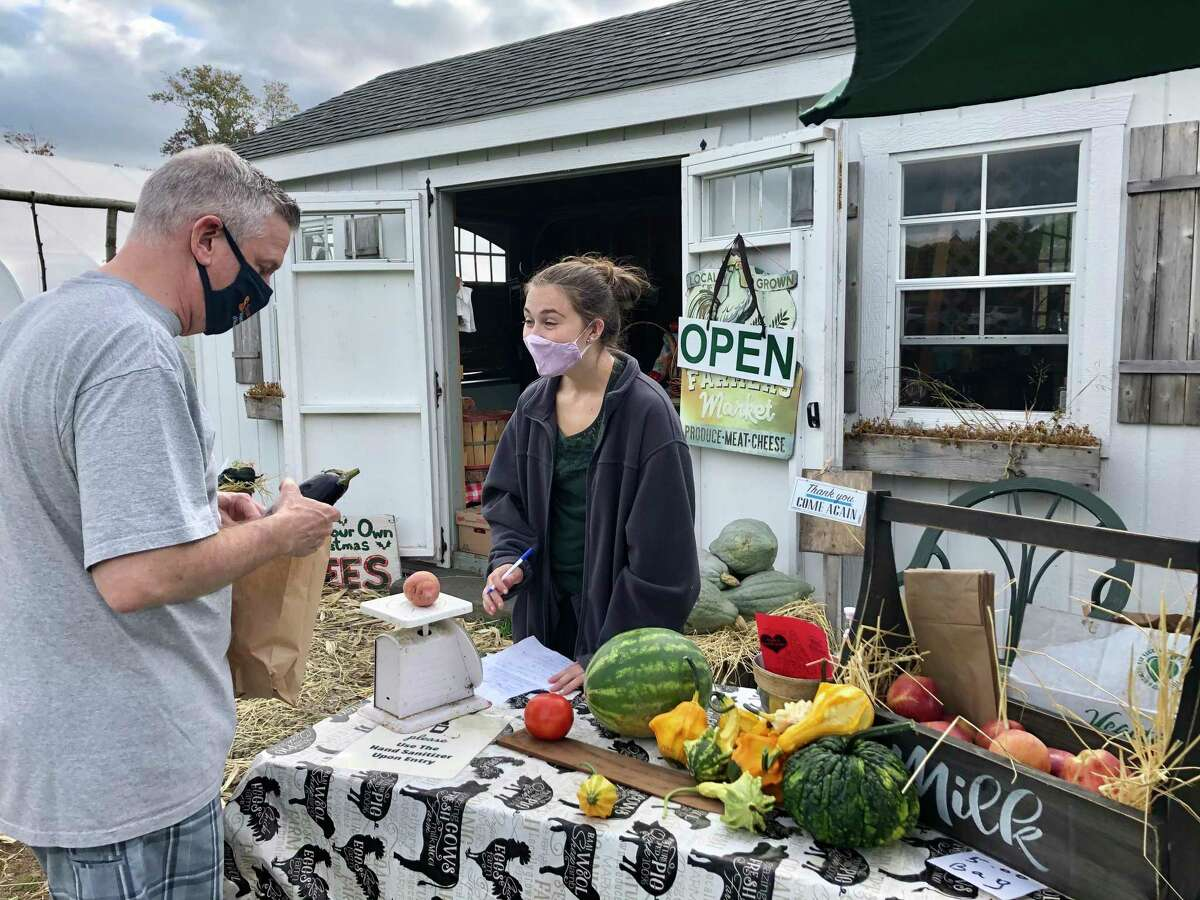 Many farms that offer pumpkin patches also have markets where you can buy fresh, home-grown produce. A visitor to Castle Hill Farm in Newtown is seen here purchasing an eggplant and other vegetables at the onsite market.