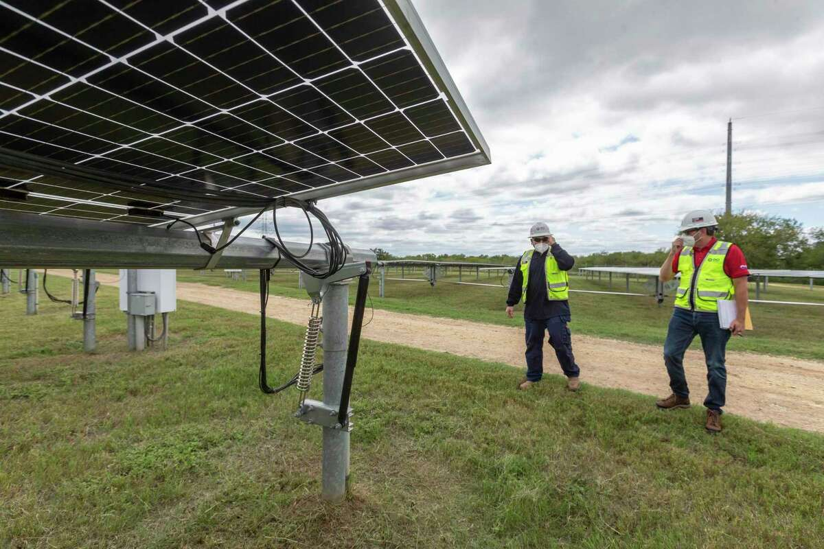 OCI Solar Power's Rico Zuniga, left, and Timothy Heinle tour the Alamo 1 solar farm on the South Side. Heinle says utilities are pursuing even larger projects now.