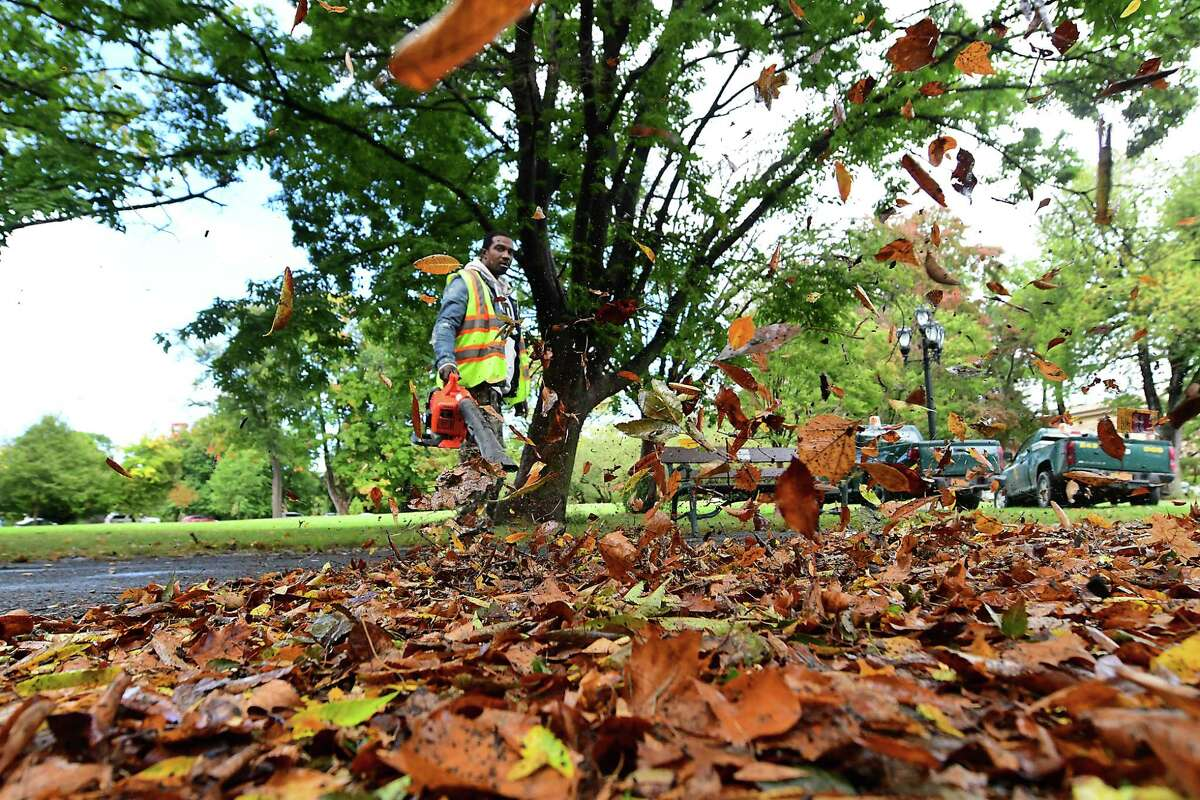 Department of General Services employee Dez Lewis uses a blower to clear fallen leaves from a walking path in Washington Park on Wednesday, Sept. 30, 2020 in Albany, N.Y. (Lori Van Buren/Times Union)