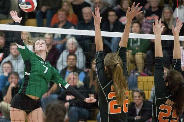 Guilford's Emma Appleman goes for the kill over Shelton's Greta Gelumbakickas(28) and Isabella Gillotti(29) during the SCC championship game Saturday night.