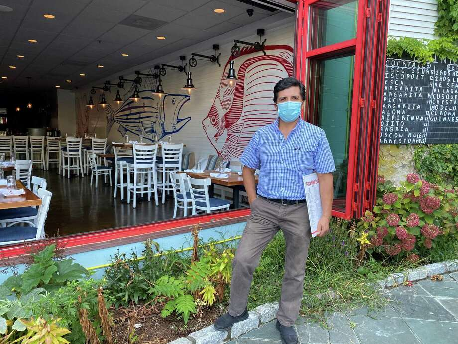 Wilson Rodriguez, co-owner of Pesca Peruvian Bistro at 70 Main St. in New Canaan, stood on the patio of the restaurant, which has large windows leading to the patio, an old fishing boat for atmosphere and large heaters outside. Photo: Grace Duffield / Hearst Connecticut Media
