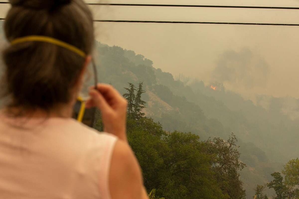 Cindy Eddy takes a photo as the Glass Fire burns the vegetation above her home and property at Rattlesnake Acres off of Highway 29, Tuesday, Sept. 29, 2020, in Calistoga, Calif.