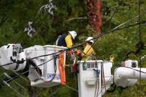 Crews work on downed power lines on South Street in Bethel on Wednesday. A violent storm that moved through the area overnight knocked out power.