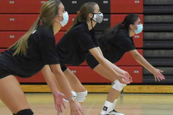 New Canaan volleyball players wear masks while awaiting a serve during a preseason practice on Friday.