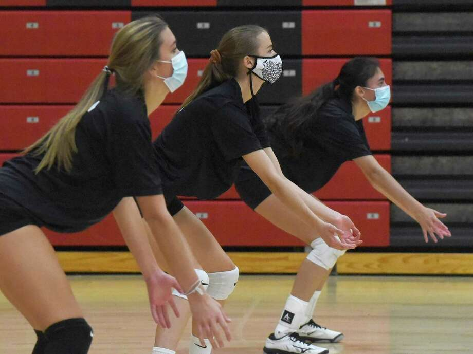 New Canaan volleyball players wear masks while awaiting a serve during a preseason practice on Friday. Photo: Dave Stewart / Hearst Connecticut Media / Hearst Connecticut Media