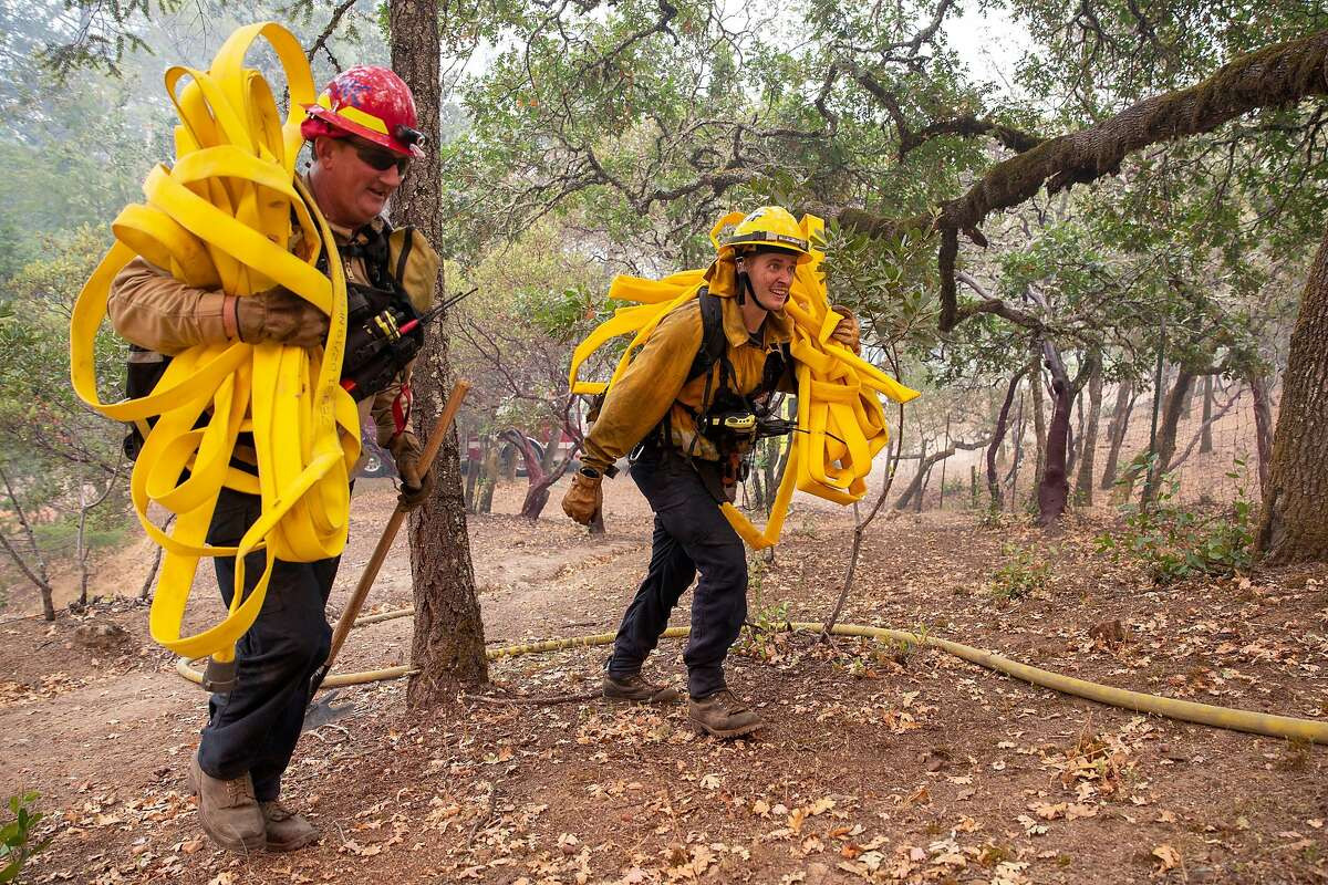San Diego County firefighters Mike Terlouw and Robert Scott carry fire hose up to a spot fire behind Schramsberg Winery during the Glass Fire in Calistoga on Tuesday.