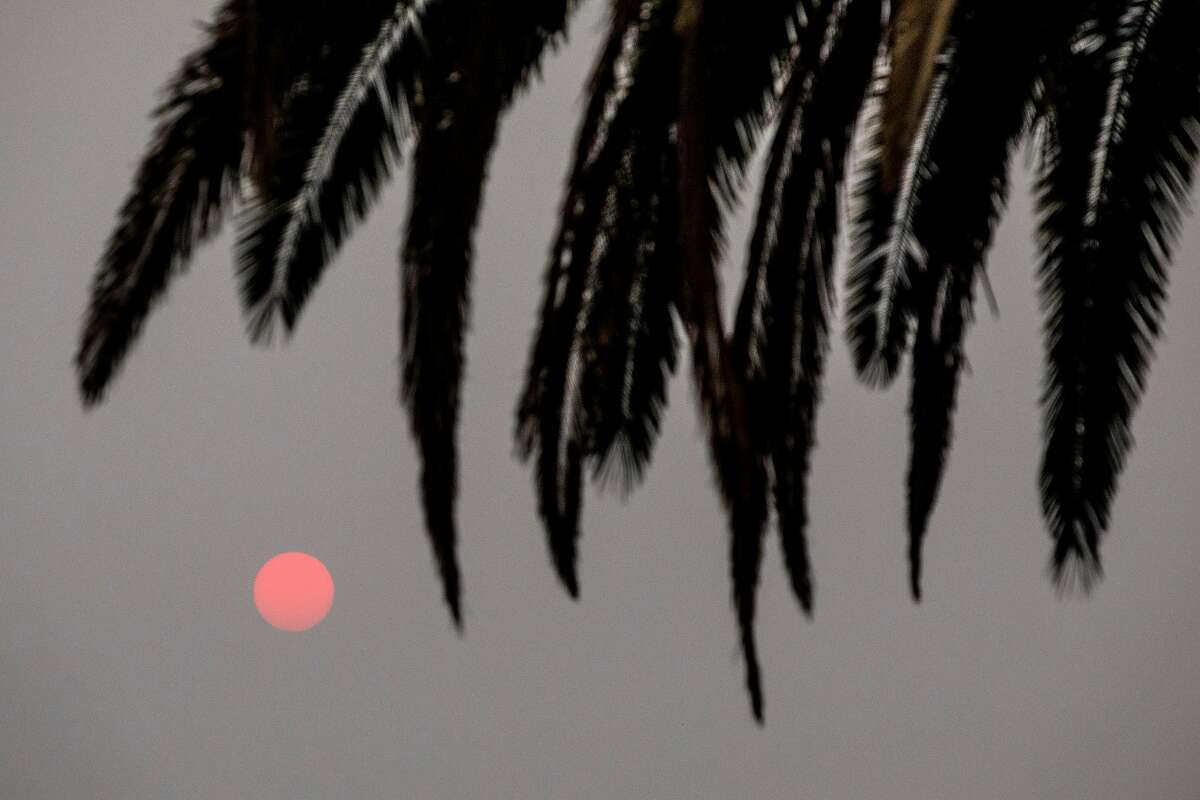 The sun rises as a red ball as the Glass Fire burns behind vineyards east of Silverado Trail in Calistoga on Tuesday.