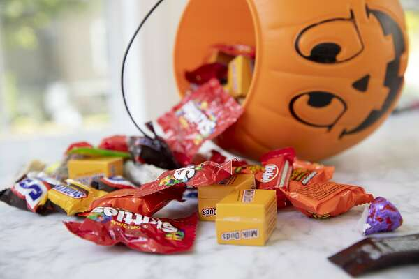 Mars Inc. and Hershey Co. brand Halloween candy is displayed for a photograph beside a pumpkin themed treat bucket in Tiskilwa, Illinois, U.S., on Sunday, Sept. 20, 2020. Costume-sellers appear to be facing one of their scariest fall seasons in a long time, even as confectioners could see sales hold steady from past years, with some candy brands even expecting an uptick. Photographer: Daniel Acker/Bloomberg