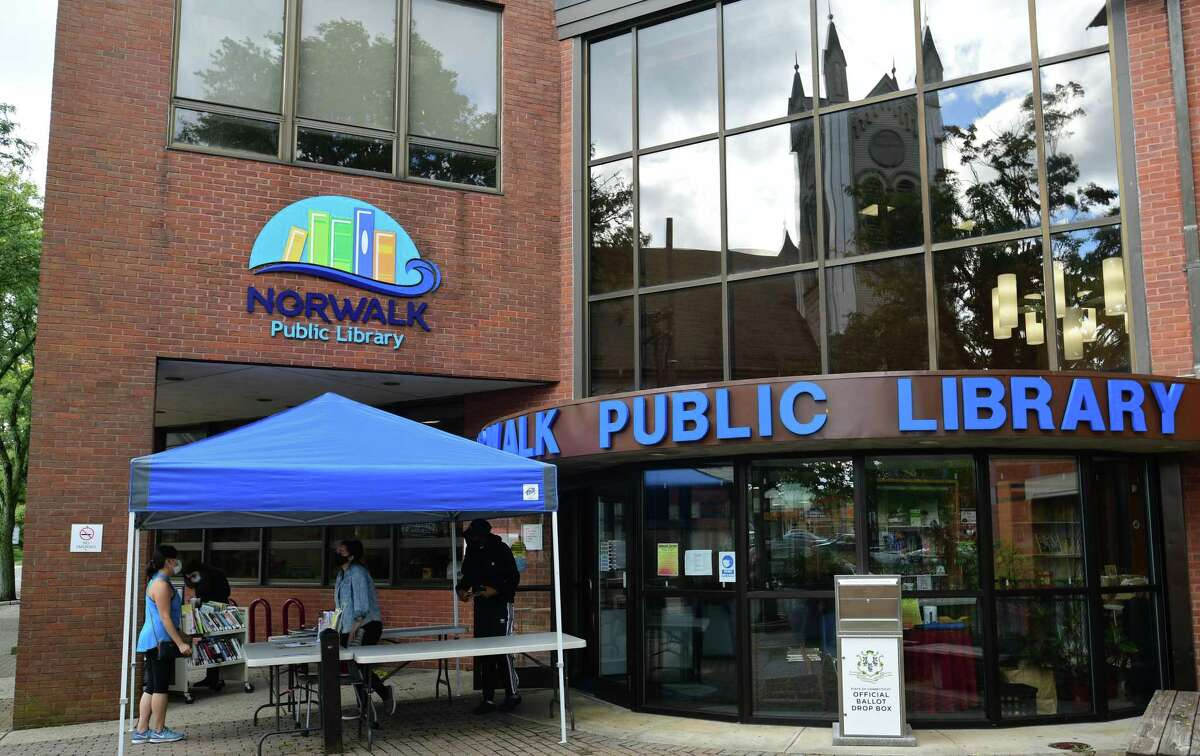Norwalk Public Library employees help patrons during the sidewalk service option offered weekdays at the main branch Wednesday, September 30, 2020, in Norwalk, Conn.
