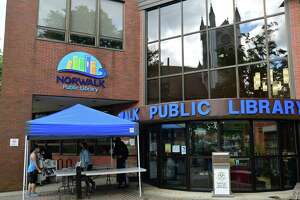 Norwalk Public Library employees help patrons during the sidewalk service option offered weekdays at the main branch Wednesday, September 30, 2020, in Norwalk, Conn. The library is reopening by appointment-only next month after months of only offering sidewalk service during the pandemic.