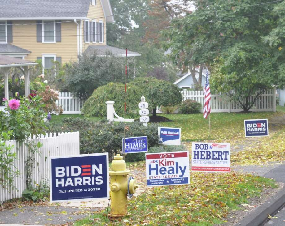 A mix of Republican and Democratic signs was visible Tuesday on Catoonah Street, where a small sign also addressed would-be sign thieves, saying their actions were disappointing. Photo: Macklin Reid / Hearst Connecticut Media