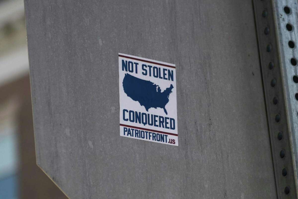 Stickers supporting the alt-right website Patriot Front are displayed on the back side of traffic signs on Greenwich Avenue in Greenwich, Conn. Monday, Sept. 28, 2020.