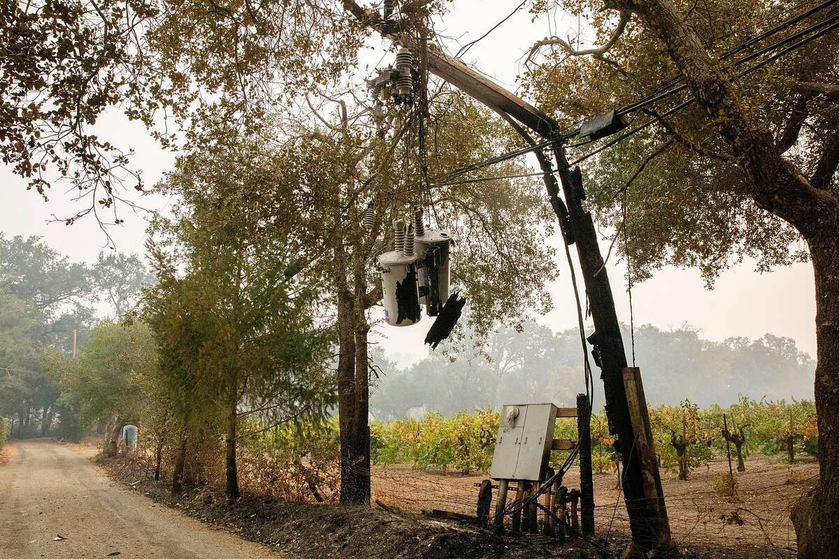 A charred utility line dangles overhead on a decimated property in Calistoga. Power lines often also carry fiber-optic lines for phone and internet service.