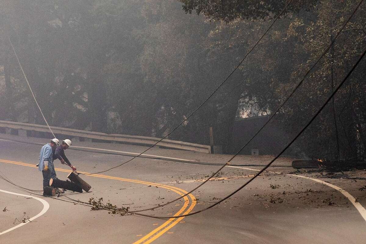 PG&E crews work to clear downed power lines along Silverado Trail as the Glass Fire burned east of Napa Tuesday. Power outages can bring down internet and cell-phone service.