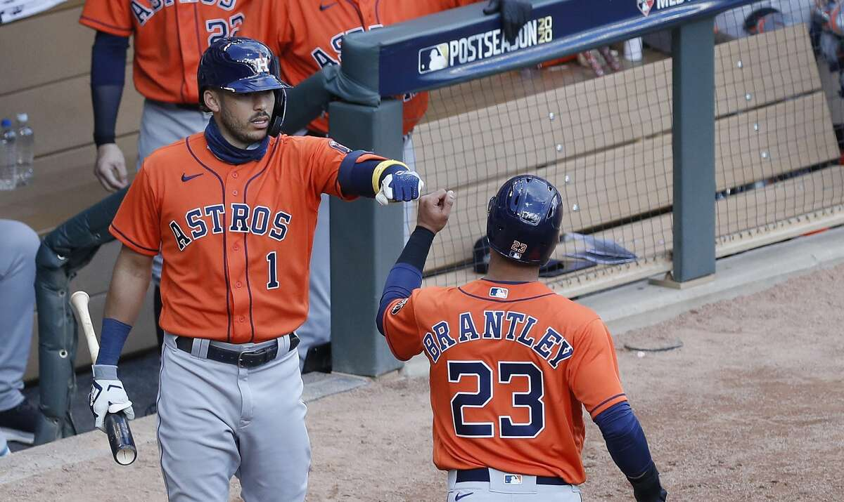 Houston Astros Michael Brantley (23) celebrates with Carlos Correa (1) after he scored a run on Kyle Tucker's RBI single during the fourth inning of Game 2 of an MLB Wild Card game at Target Field, Wednesday, September 30, 2020, in Minneapolis.