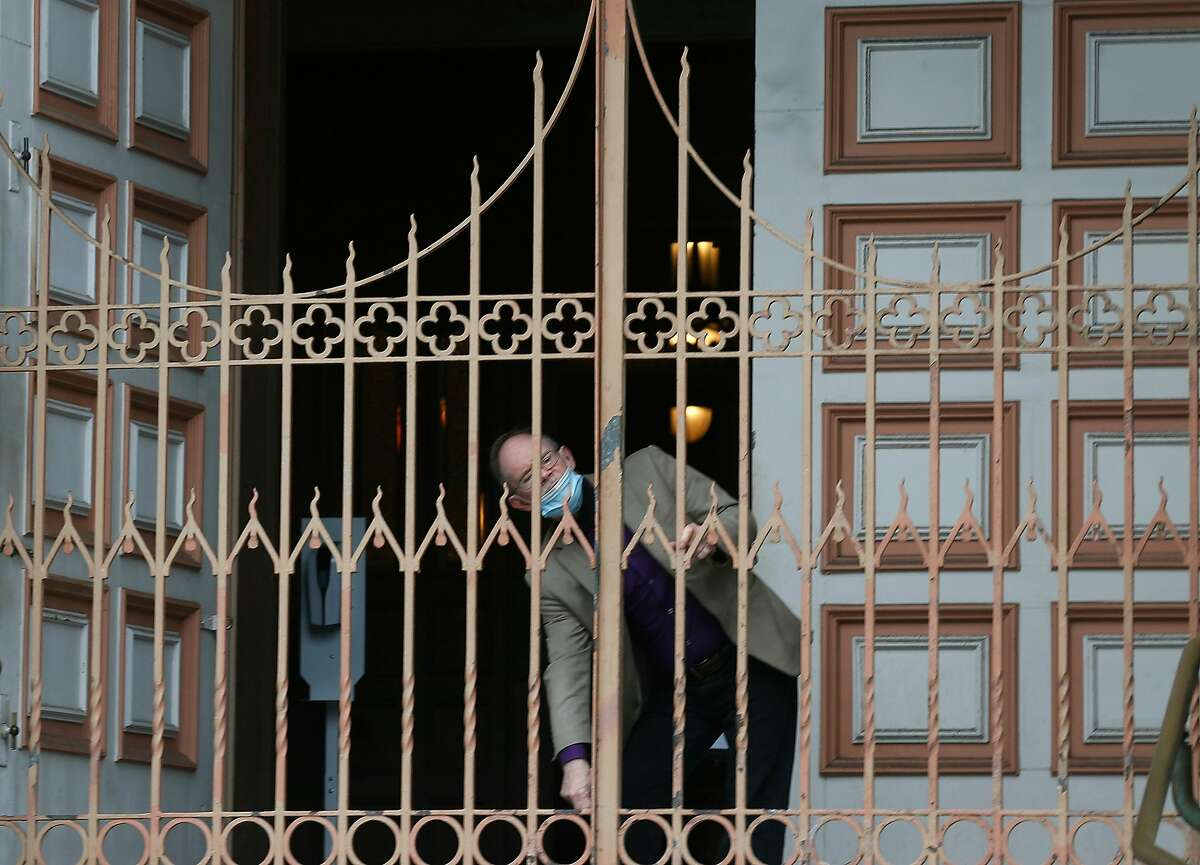 The Parish Secretary unlocks the gate at Ss. Peter & Paul church in San Francisco, Calif. San Francisco advances to California's least-restrictive tier for reopening, expanding access to indoor climbing gyms, movie theaters, houses of worship and more.