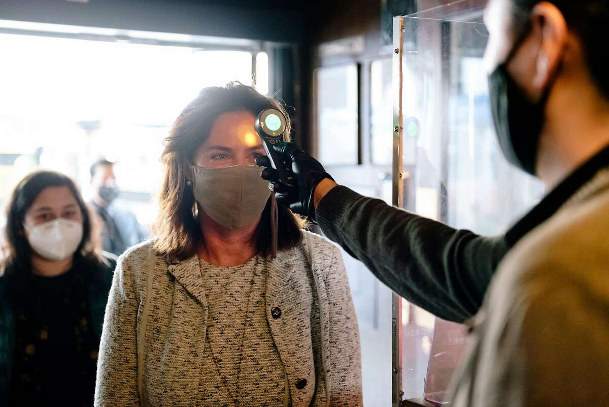 Guest Karin Flood has her temperature taken by manager Christian Renteria upon entering at John's Grill in San Francisco in September.