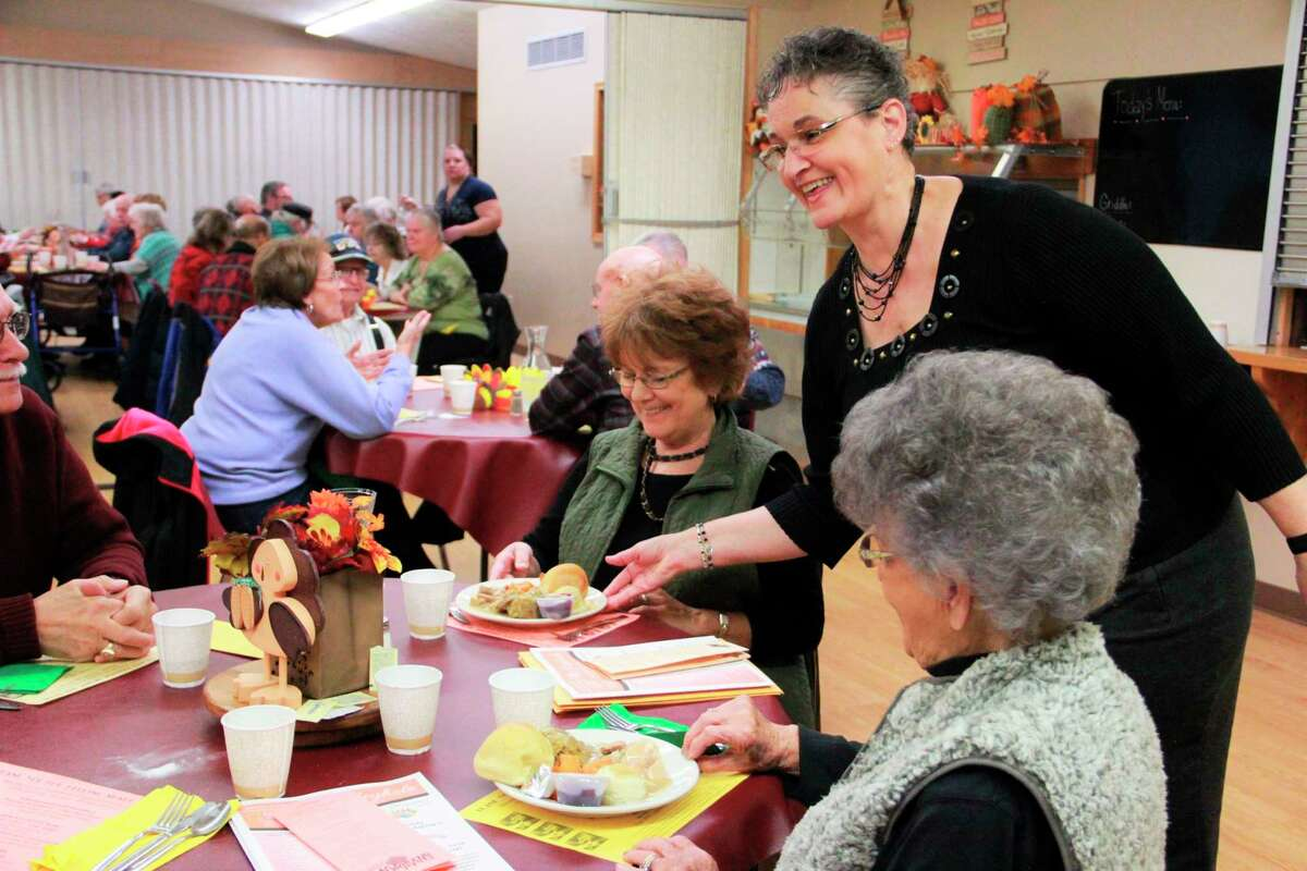 In this file photo, a COA volunteer mingles with guests during last year's Thanksgiving Feast. According to a release provided by the COA, anyone interested in volunteering their time, while making extra money, are welcome to contact Jo Ann Longcor at 231-972-2884 for more information on their Home Maintenance Program. (Pioneer file photo)