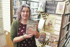 """Amy Gibbons, circulation clerk at the Wood River Library, holds a copy of Harper Lee's """"To Kill a Mockingbird,"""" one of the books from a display on """"Banned Books Week,"""" which runs through Oct. 3."""