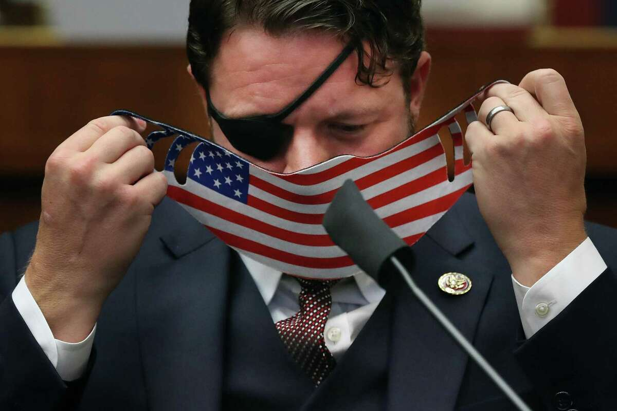 House Homeland Security Committee member Rep. Dan Crenshaw (R-TX) replaces his face mask during a hearing on 'worldwide threats to the homeland' in the Rayburn House Office Building on Capitol Hill September 17, 2020 in Washington, DC.