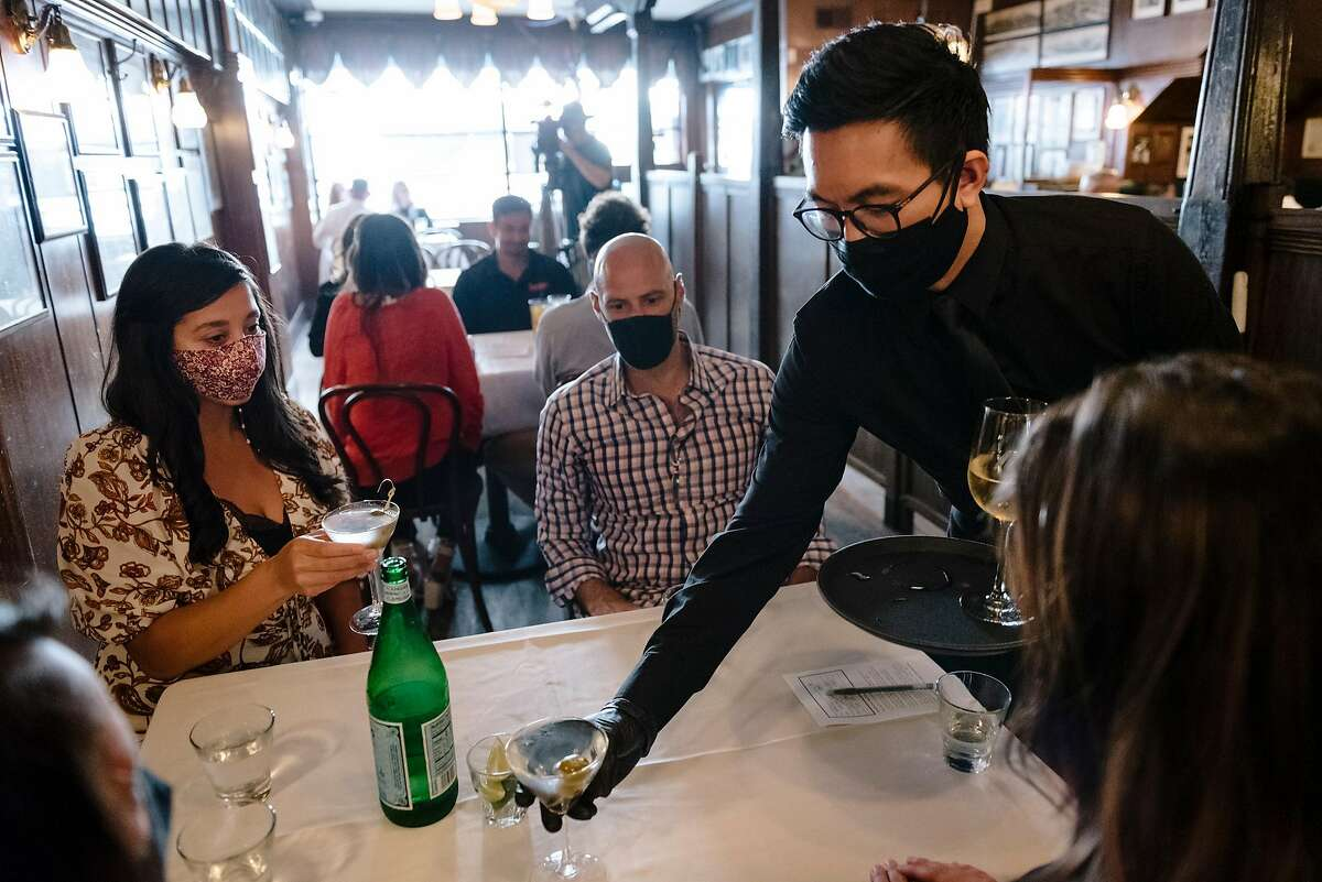 Server Nat Chananudech wears a mask and gloves as he delivers drinks to guests at John's Grill in San Francisco in September.