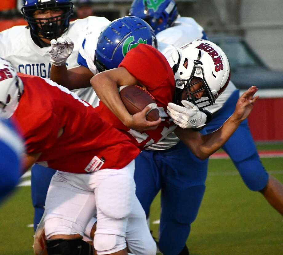 Lockney's Anson Rendon fights off a Compass Academy defender on a rushing attempt during their non-district high school football game on Sept. 25, 2020 at Lockney. Photo: Nathan Giese/Planview Herald