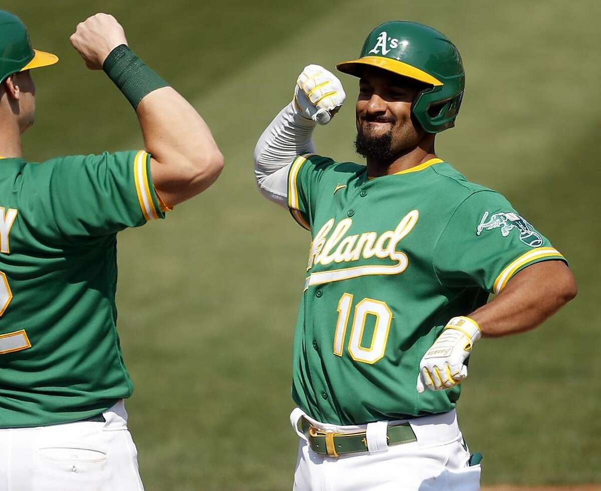 Oakland Athletics' Marcus Semien arm, bumps Sean Murphy after Semien's 2-run home run in 2nd inning again st Chicago White Sox during American League Wild Card Series Game 2 at Oakland Coliseum in Oakland, Calif., on Wednesday, September 30, 2020.