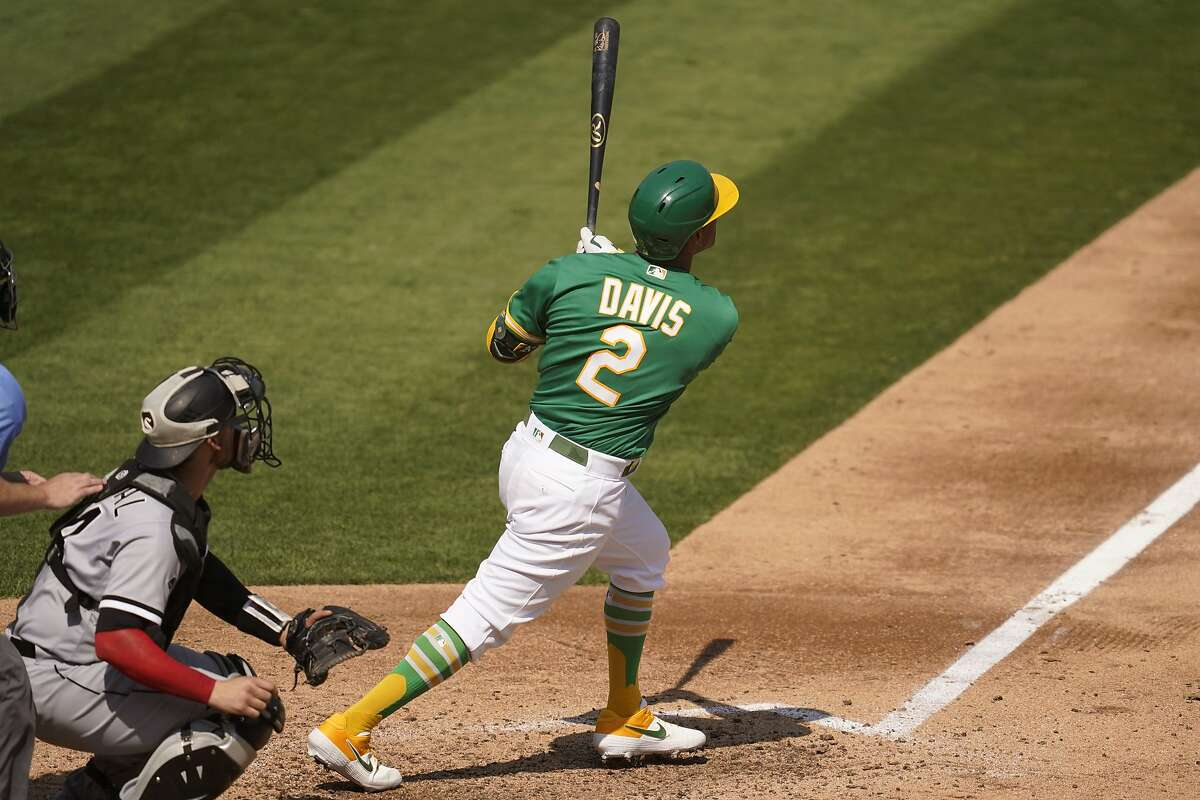 Oakland Athletics' Khris Davis (2) hits a solo home run in front of Chicago White Sox catcher Yasmani Grandal during the fourth inning of Game 2 of an American League wild-card baseball series Wednesday, Sept. 30, 2020, in Oakland, Calif. (AP Photo/Eric Risberg)