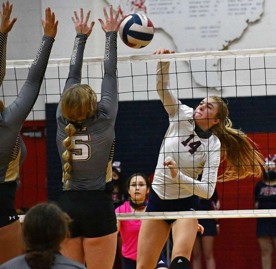 Plainview's Saige Brunson hits a ball past a pair of Lubbock defenders during their non-district high school volleyball match on Sept. 29, 2020 in the Dog House at Plainview High School. Photo: Nathan Giese/Planview Herald