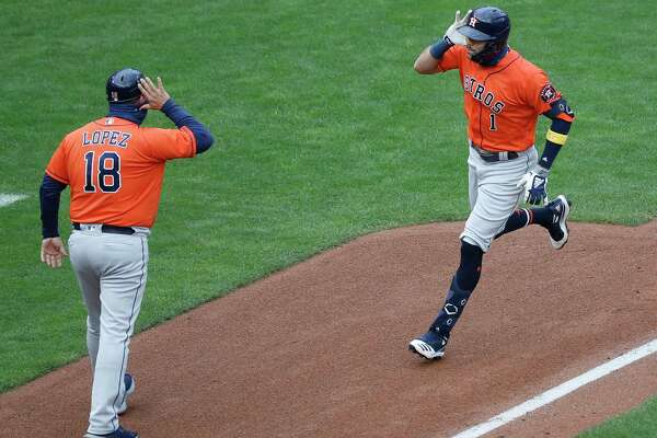 Houston Astros Carlos Correa (1) celebrates with third base coach Omar Lopez after hitting a solo home run during the seventh inning of Game 2 of an MLB Wild Card game at Target Field, Wednesday, September 30, 2020, in Minneapolis.