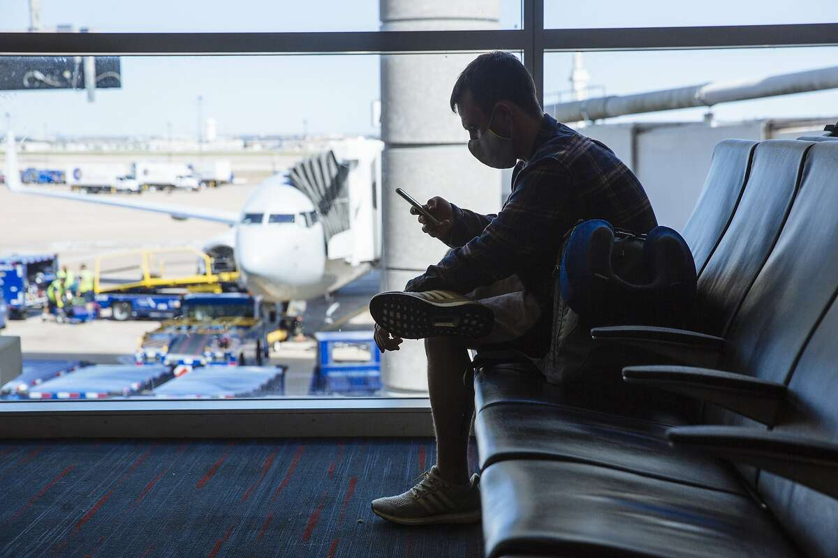 A traveler wearing a protective mask views a smartphone while waiting for a flight at Dallas/Fort Worth International Airport (DFW) in Dallas on Monday, Sept. 28, 2020.