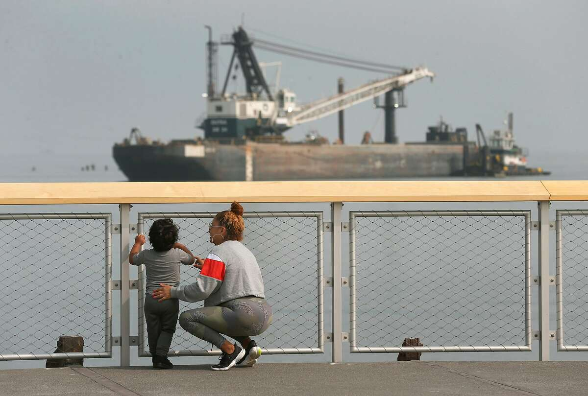 Laura Santiago and her son Anthony Gutierrez admire the view of boats and barges on the bay at the new Crane Cove Park in San Francisco.