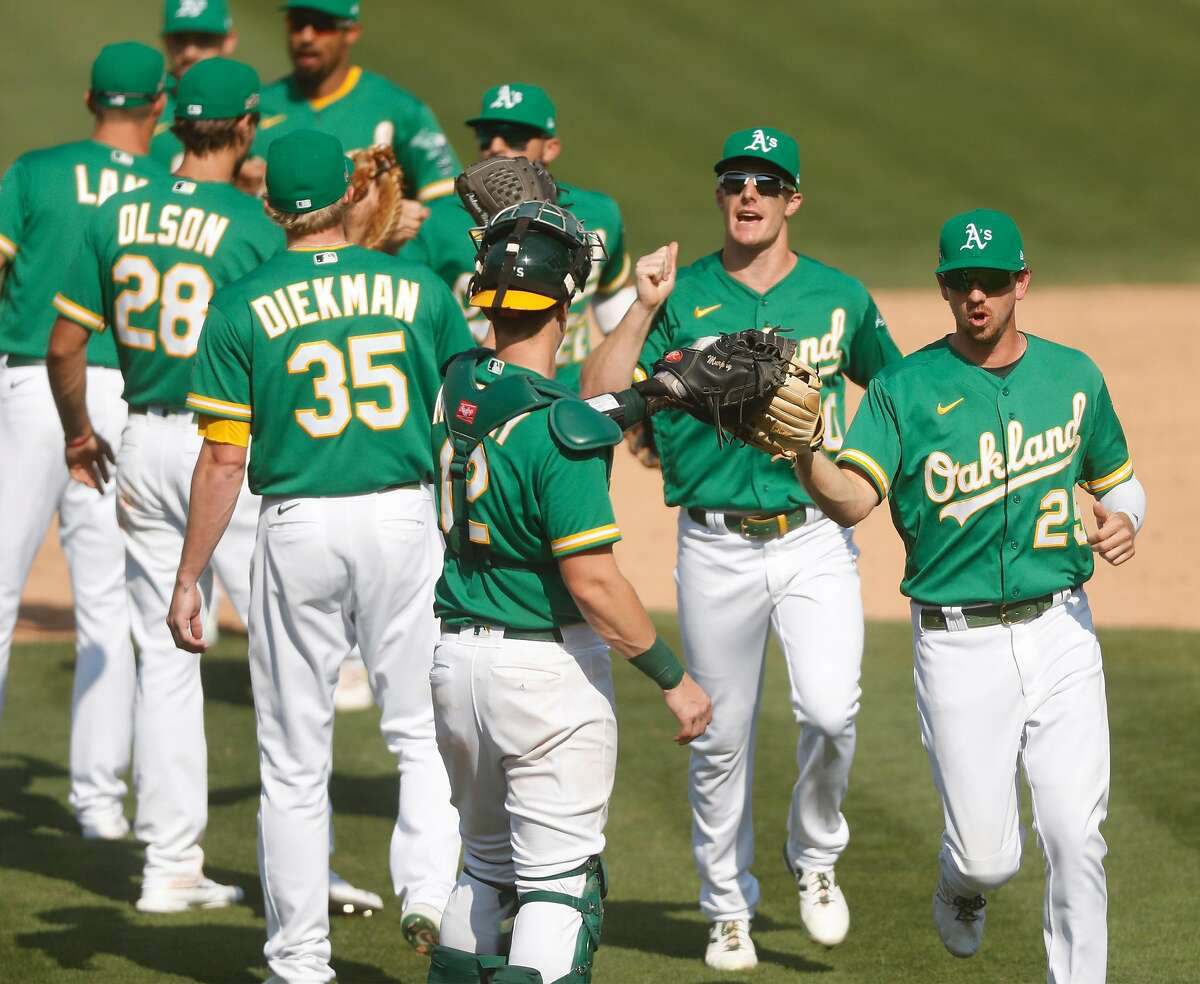 Oakland Athletics' Stephen Piscotty and Mark Canha celebrate with teammates after 5-3 win over Chicago White Sox in American League Wild Card Series Game 2 at Oakland Coliseum in Oakland, Calif., on Wednesday, September 30, 2020.