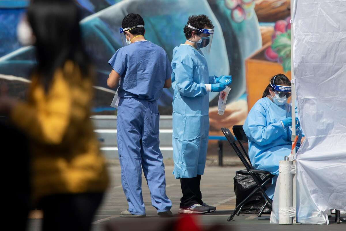 Volunteers and staff with UCSF move people through a coronavirus testing site in the Mission District.