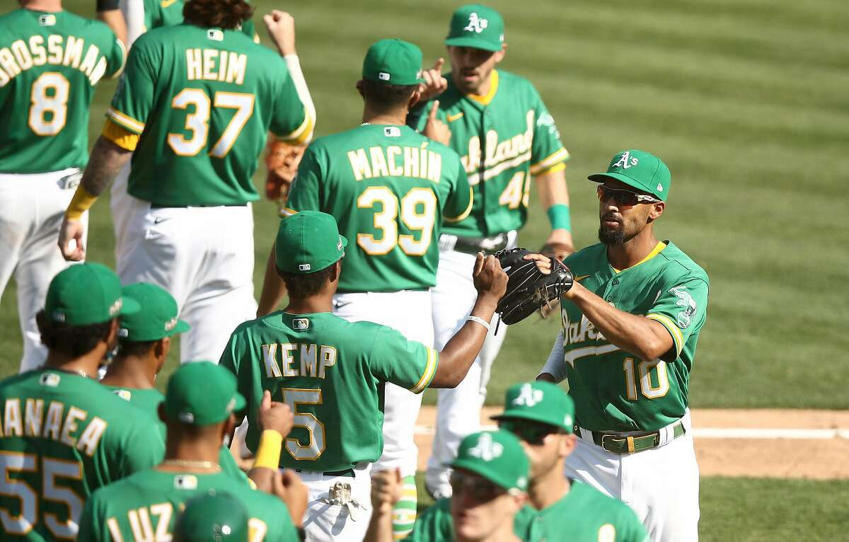 The Oakland Athletics' Tony Kemp (5) and Marcus Semien (10) high-five in the middle of a celebration of a 5-3 win against the Chicago White Sox in Game 2 of the American League Wild Card Round on Wednesday, Sept. 30, 2020, at RingCentral Coliseum in Oakland, California. (Ezra Shaw/Getty Images/TNS)