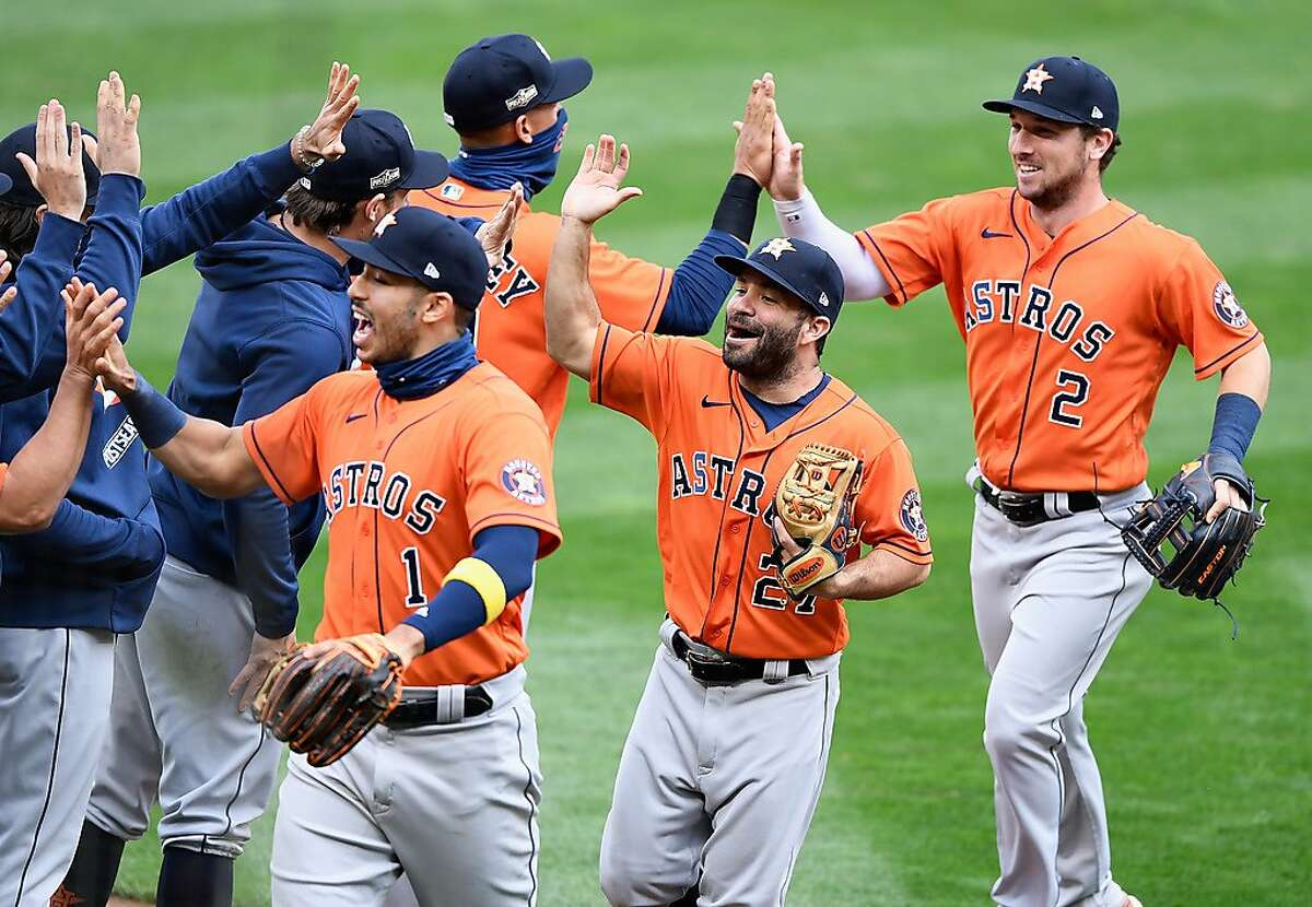 Astros infielders Carlos Correa (left), Jose Altuve and Alex Bregman greet teammates after they eliminated the Minnesota Twins with a 3-1 win in the second game of their wild-card series at Target Field in Minneapolis.