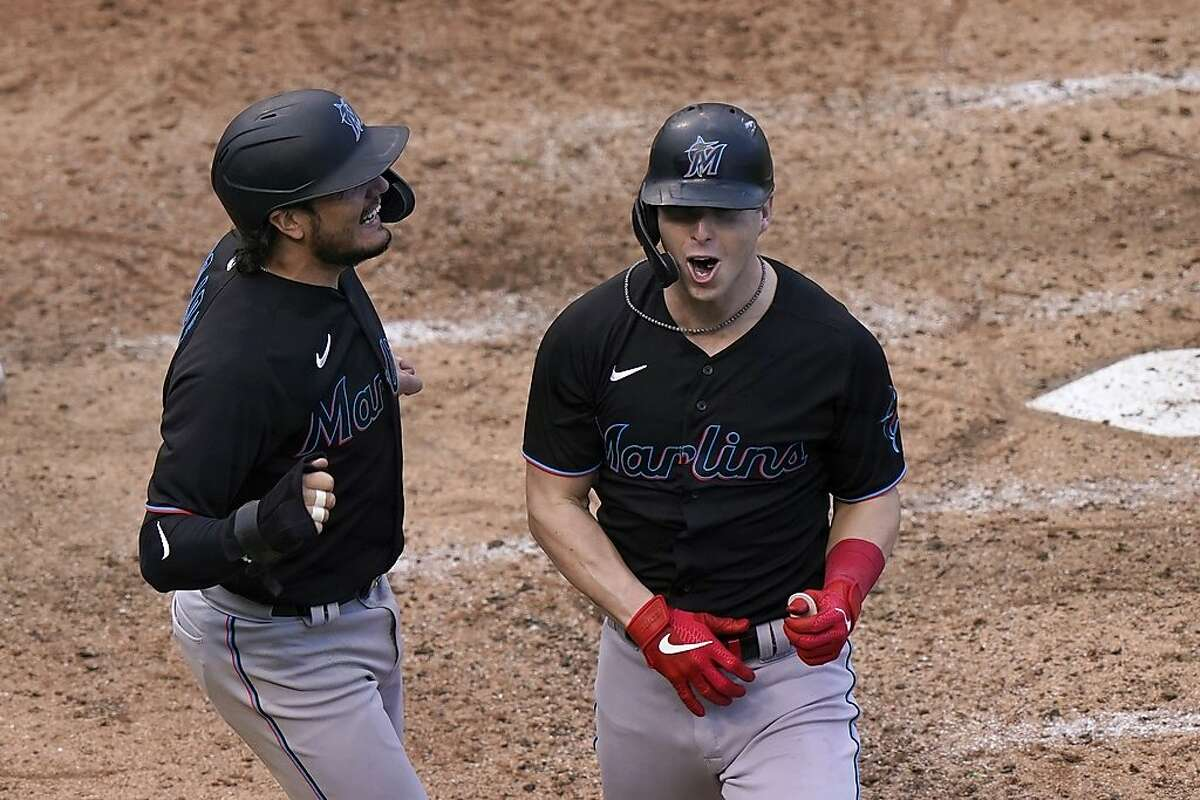 Miami Marlins' Miguel Rojas (19) celebrates with Corey Dickerson, right, after Dickerson hit a three-run home run that scored Rojas and Chad Wallach in the seventh inning of Game 1 of a National League wild-card baseball series against the Chicago Cubs in Chicago, Wednesday, Sept. 30, 2020. (AP Photo/Nam Y. Huh)