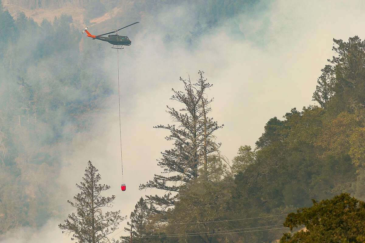 A helicopter drops water on the Glass Fire east of Highway 29 in Calistoga.