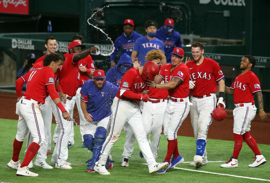 ARLINGTON, TEXAS - SEPTEMBER 25: The Texas Rangers celebrate the win over the Houston Astros after a walk off single by Joey Gallo #13 of the Texas Rangers that scored Isiah Kiner-Falefa in the 10th inning at Globe Life Field on September 25, 2020 in Arlington, Texas. Photo: Richard Rodriguez/Getty Images / 2020 Richard Rodriguez