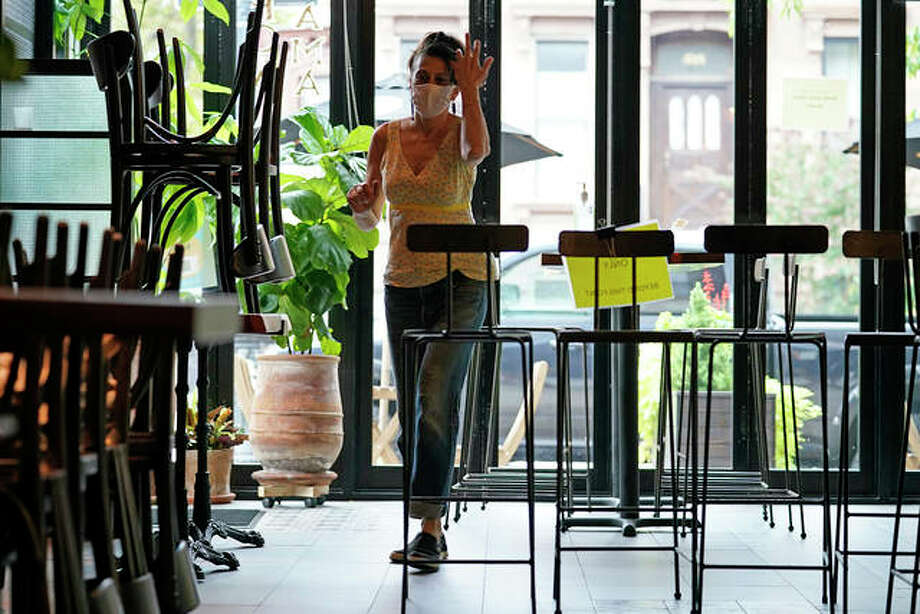 Chairs are still placed atop tables and lined up to form a border as Samantha DiStefano walks through her restaurant and bar while preparing for indoor dining. Photo: Kathy Willens | AP