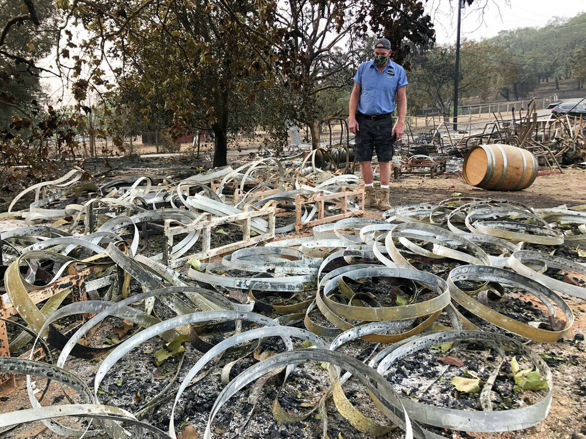 """Kevin Conant looks down at hundreds of burnt metal rings left from burned wine barrels at his business """"Conants Wine Barrel Creations,"""" after the Glass/Shady fire completely engulfed it in Santa Rosa, Calif., Wednesday, Sept. 30, 2020. The Conants escaped with their lives, which we are grateful for, but they barely made it out with the clothes on their backs in the wake of the fire. The Glass and Zogg fires are among nearly 30 wildfires burning in California."""