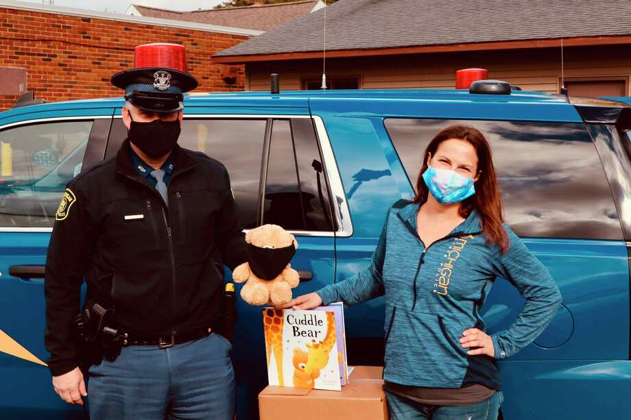 Trooper Corey Hebner and Ashley Brown with a Cuddle Bear and accompanying book she helped raise money for to give to children that are victims or witnesses to crime. (Courtesy Photo)