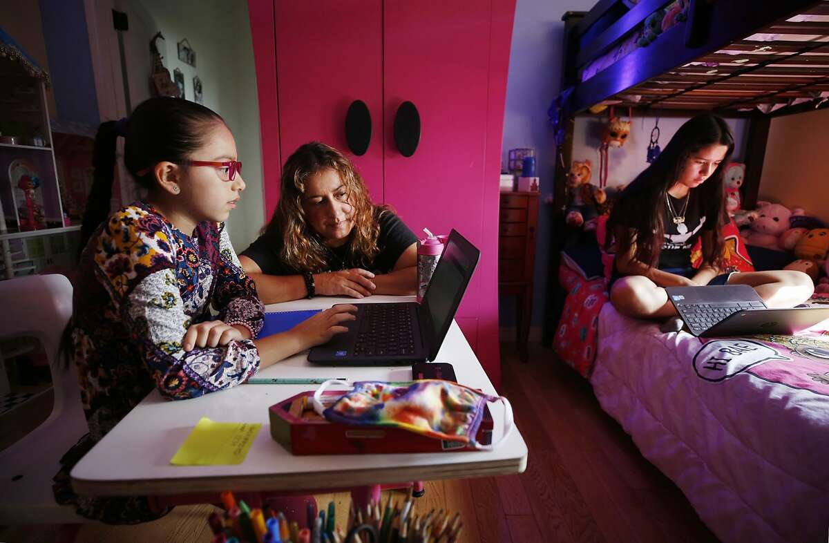 Sofia Quezada assists her daughters Priscilla, left, and Paulette Guerrero with virtual class from their Boyle Heights home. Tech issues on the first day of class drove 9-year-old Priscilla to tears.(Al Seib/Los Angeles Times/TNS)